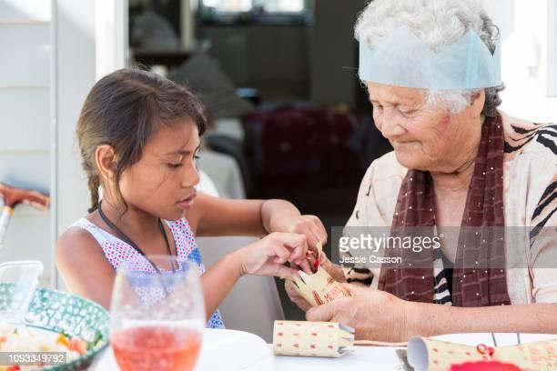 Kid and grandma opening Christmas cracker