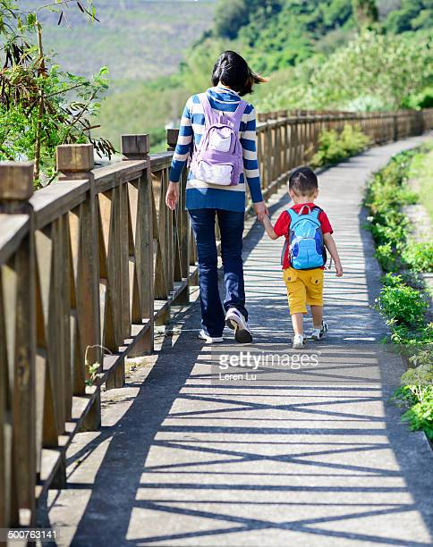 kid and mom holding hands and walking - leren stock pictures, royalty-free photos & images