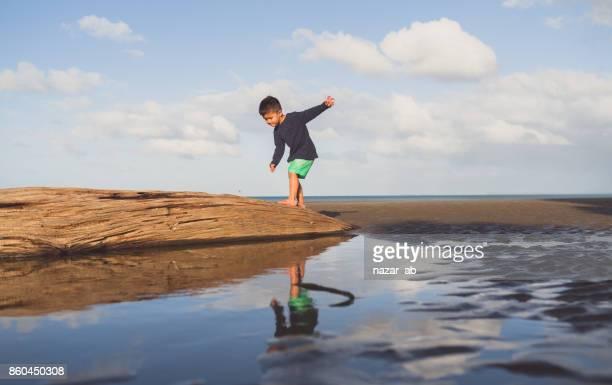 Kid balancing up himself on log at beach.