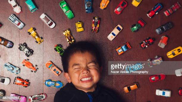 Kid Being Cheek Lying On Floor With His Cars Around Him.