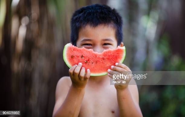 Kid being cheeky while eating watermelon.