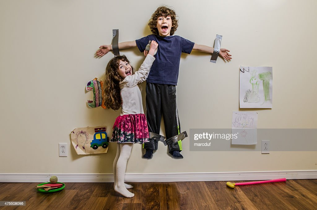 Kid being duct taped on wall by his sister : Stock Photo