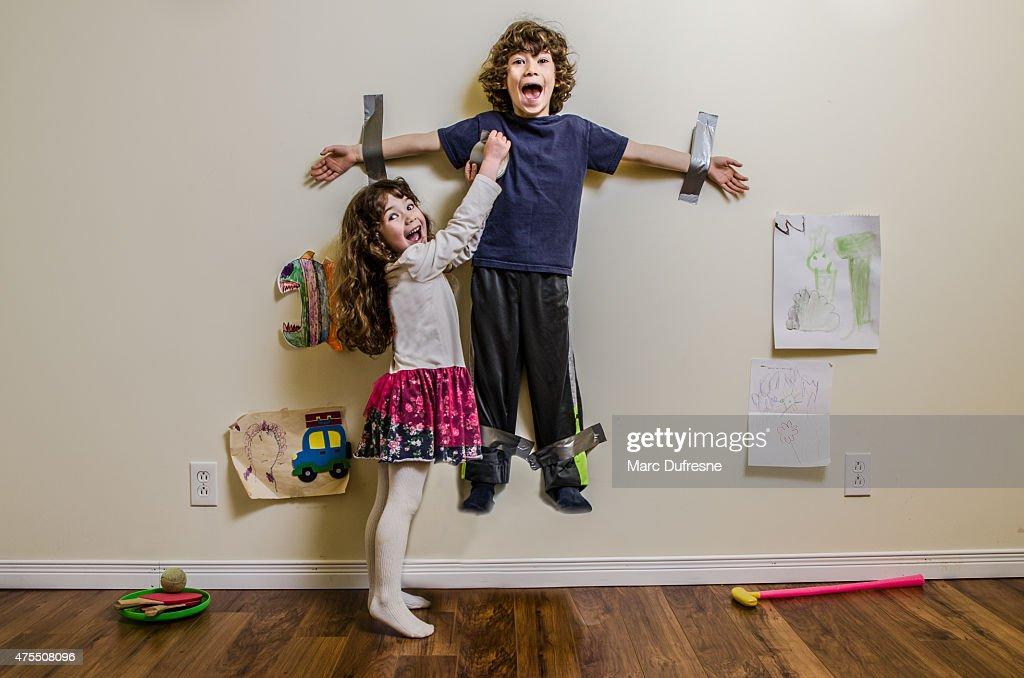 Kid, Duktus verschweißte an der Wand durch seine Schwester : Stock-Foto