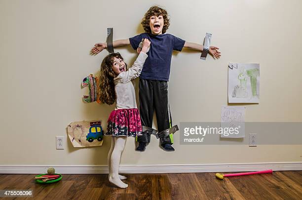 kid being duct taped on wall by his sister - opstand stockfoto's en -beelden