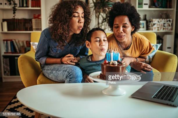 kid blowing candle for his birthday during pandemic - birthday candle stock pictures, royalty-free photos & images