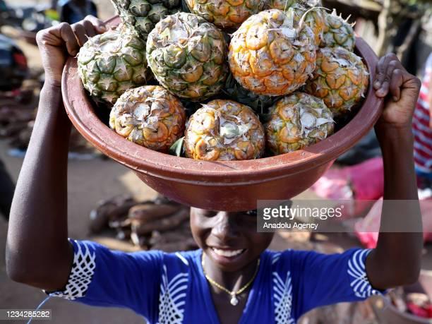 Kid carries a basket of fruit on his head in Abidjan, Ivory Coast on July 28, 2021.