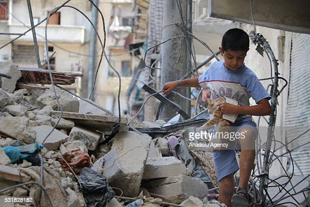 A kid carrying a cat walks inside the debris of collapsed buildings after Assad Regime's attack with a highlyexplosive localmade missile called the...