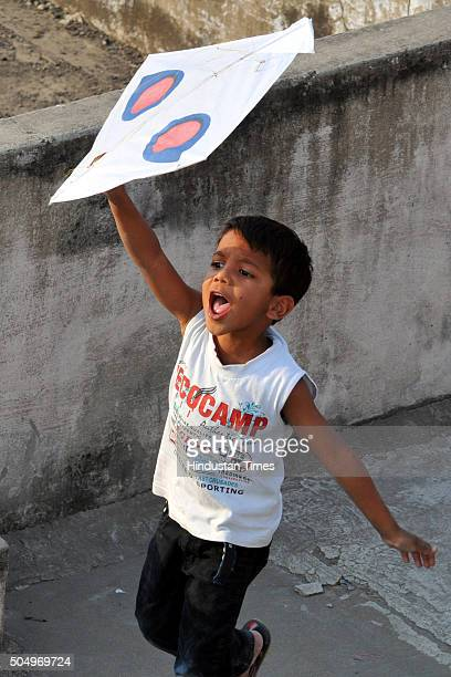 A kid catches a kite on the eve of Makar Sankranti on January 14 2016 in Indore India The festival of harvest 'Makar Sankranti' is being celebrated...