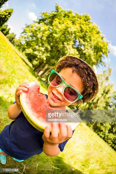 Kid cheerfully eating a watermelon on hot summer day