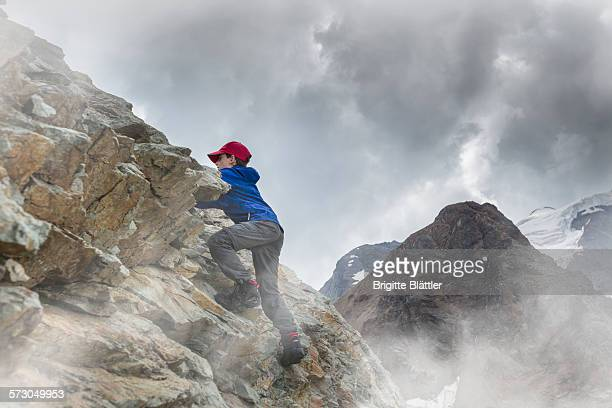 Kid climbing on rock, Engadin, Switzerland.