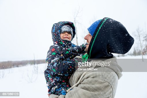 Kid covered with snow laughing with his father.