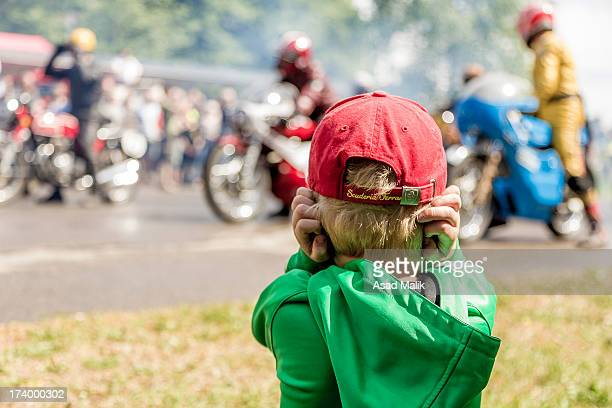 Kid covering his ears because of the noise from the old bikes