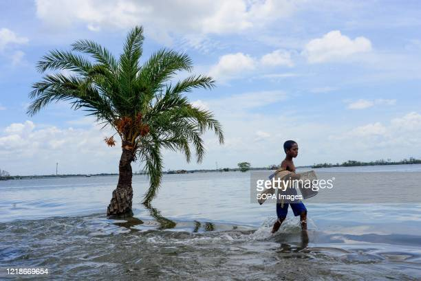 Kid crosses a broken flooded road after the landfall of cyclone Amphan during the aftermath. Thousands of shrimp enclosures have been washed away,...