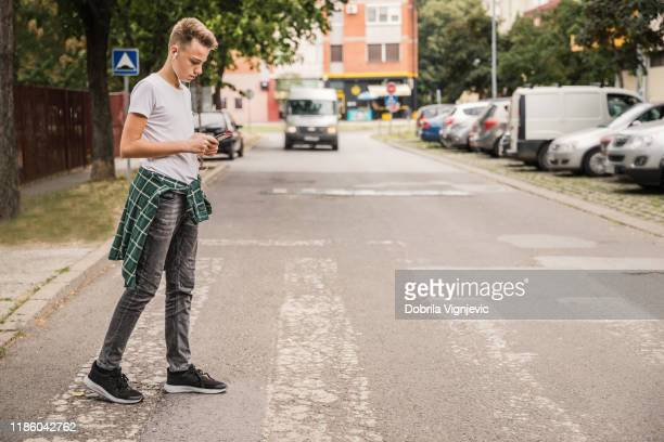 kid crossing the street at a pedestrian crossing and listening to music on his cellphone - pedestrian stock pictures, royalty-free photos & images