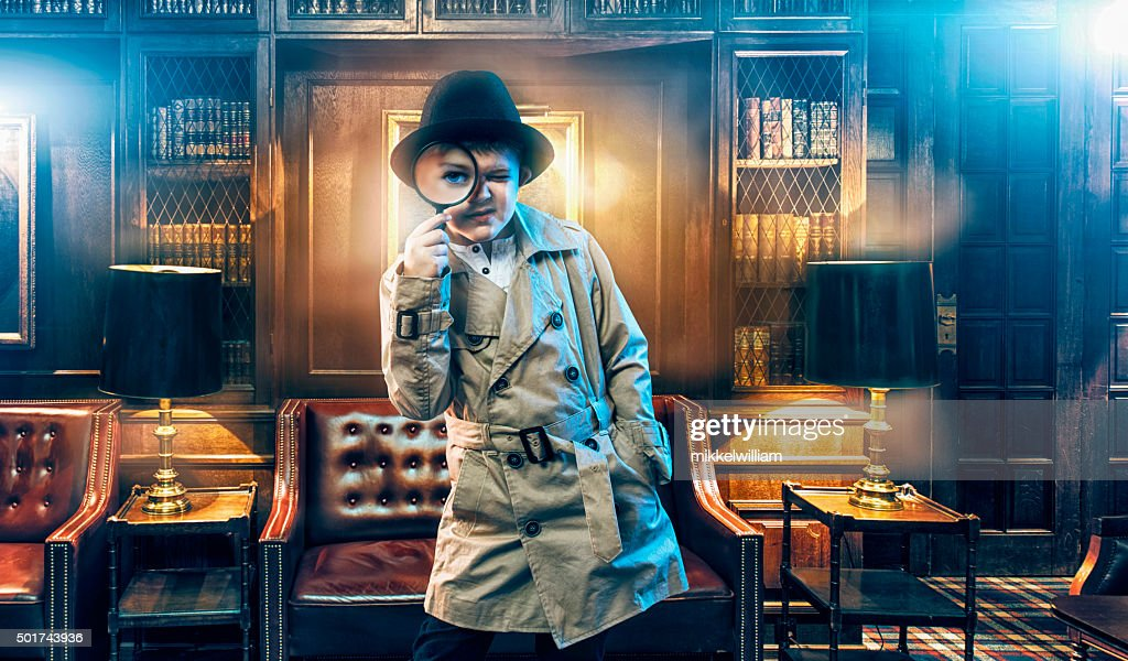 Kid detective wears trench coat and searches for clues : Stock Photo
