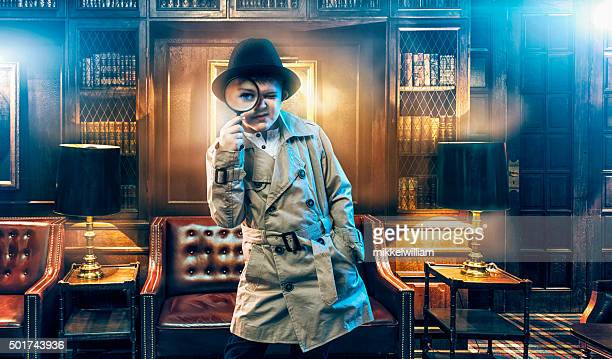 kid detective wears trench coat and searches for clues - mystery stock pictures, royalty-free photos & images