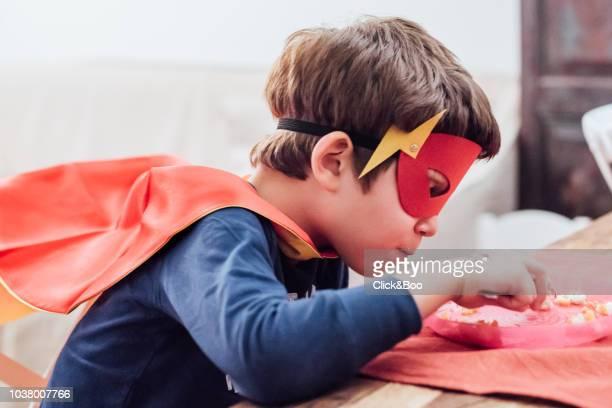 Kid disguised as a superhero having dinner (home interior)