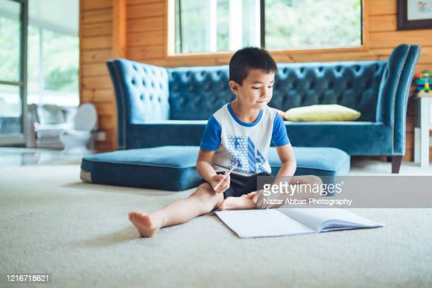 kid doing home work at home. - nazar abbas photography stock pictures, royalty-free photos & images