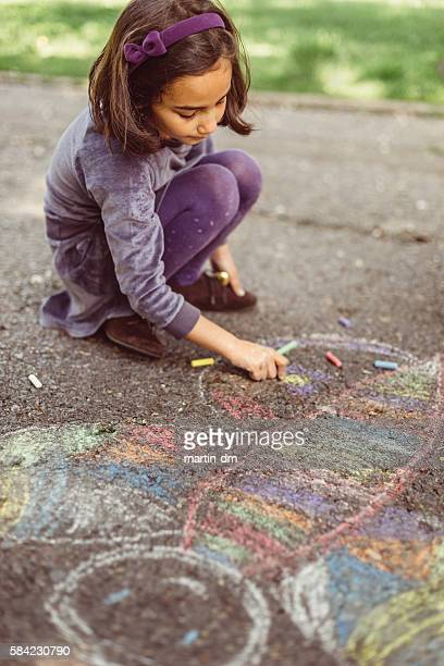 Kid drawing with chalk on asphalt