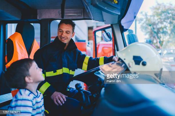 kid dreaming to be a firefighter - firefighter stock pictures, royalty-free photos & images