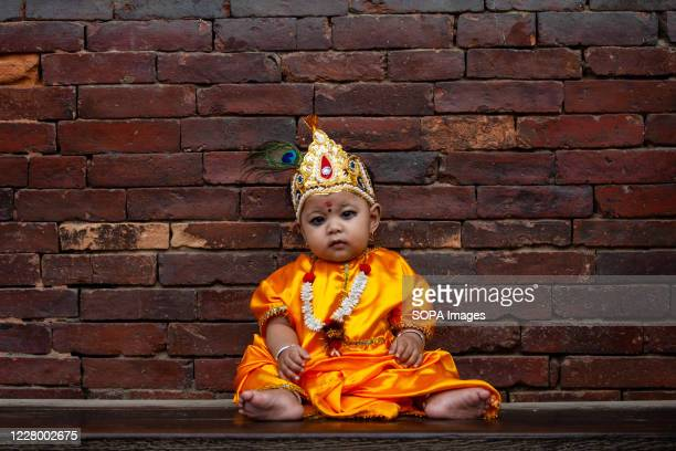 A kid dressed as Lord Krishna sits outside of the Krishna Mandir during the festival at Patan Durbar Square Krishna Janmashtami is an annual Hindu...