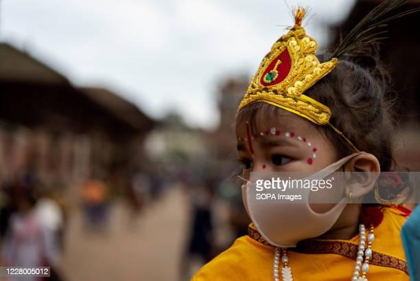 A kid dressed as Lord Krishna wearing a face mask during the festival at Hanuman Dhoka Sadak near Kathmandu Durbar Square Krishna Janmashtami is an...