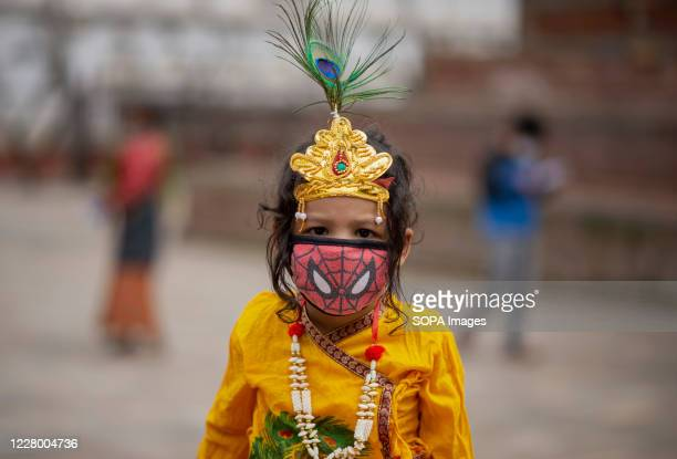 A kid dressed as Lord Krishna wearing a spiderman face mask during the festival at Hanuman Dhoka Sadak near Kathmandu Durbar Square Krishna...