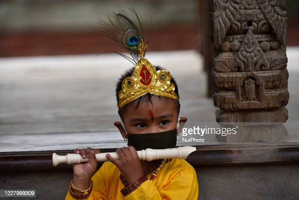 A Kid dressed as the Hindu god Krishna along with face mask during Krishna Janmashtami in Patan Durbar Square Lalitpur Nepal on Tuesday August 11...