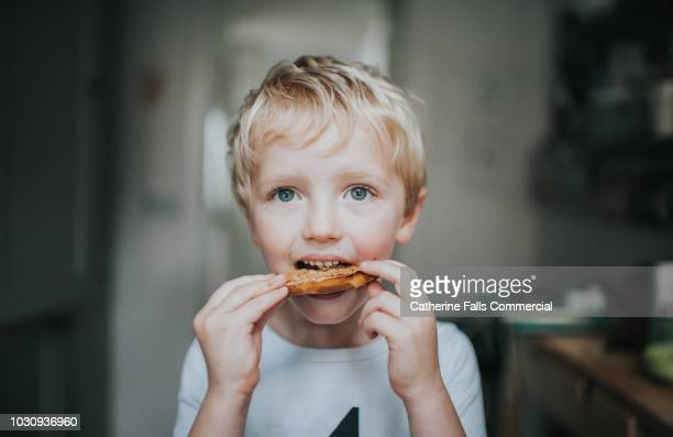kid eating a bagel - nut food stock photos and pictures