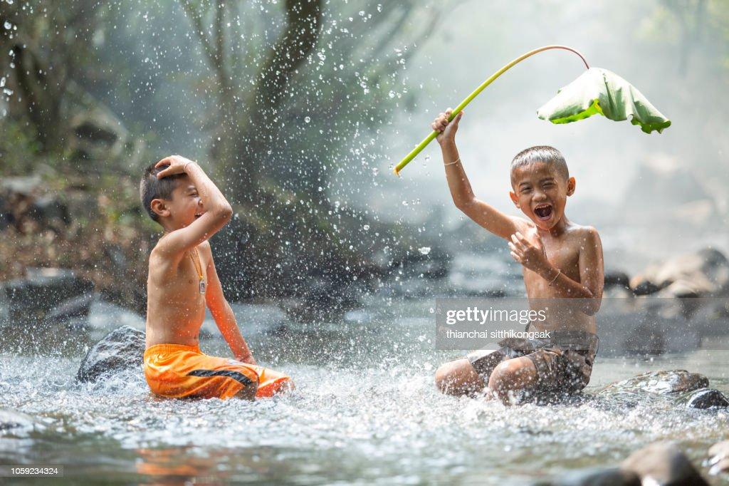 kid enjoy playing splashing water : Stock Photo