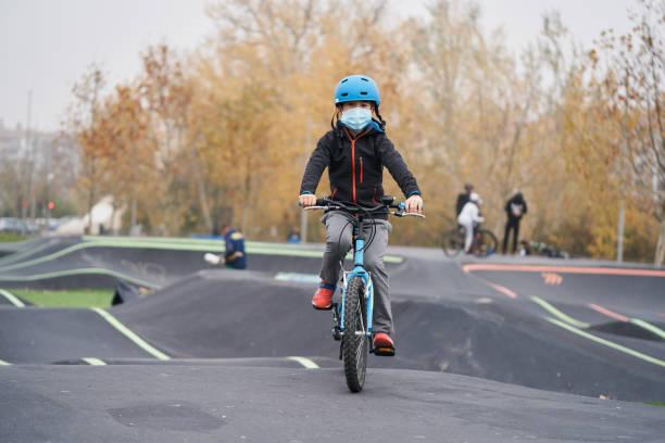 Kid enjoying while riding a bike on a pumptrack.