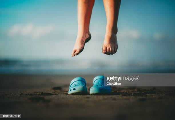 kid feet on the beach jumping on his blue clogs - open toe stock pictures, royalty-free photos & images