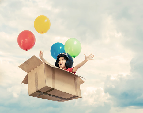 Kid flying in cardboard box with balloons between clouds - gettyimageskorea