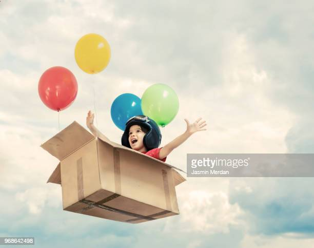 kid flying in cardboard box with balloons between clouds - vorstellungskraft stock-fotos und bilder