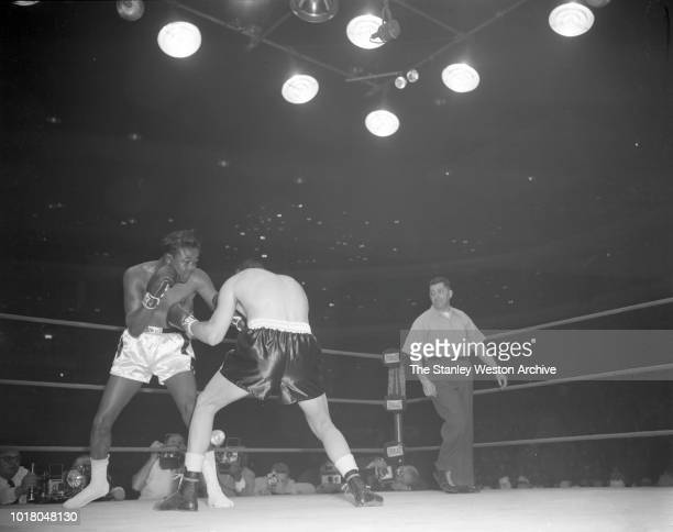 Kid Gavilan and Bobo Olson exchange punches as referee Bernie Weismann watches the action in Chicago Stadium Chicago Illinois April 2 1954 Bobo Olson...