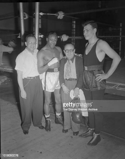 Kid Gavilan and trainer Charley Goldman center pose for a portrait with fellow boxers and trainers in Stillman's Gym circa 1955 in New York City New...
