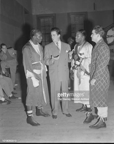 Kid Gavilan and two fellow boxers in their robes are talking with a gentleman in Stillman's Gym circa 1955 in New York City New York