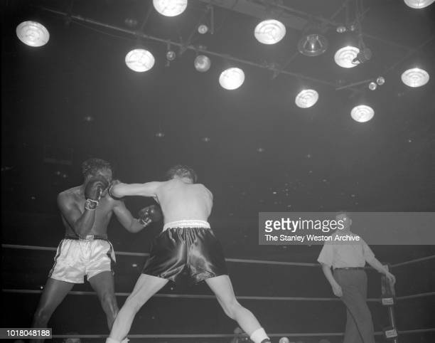 Kid Gavilan tries to dodge a left hook delivered by Bobo Olson as referee Bernie Weismann watches the action in Chicago Stadium Chicago Illinois...