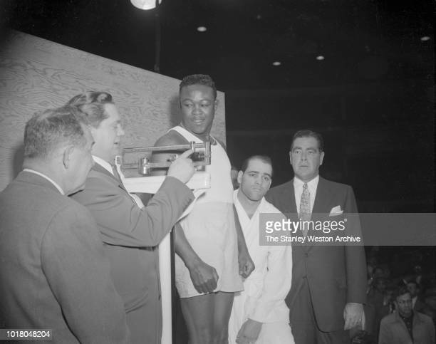 Kid Gavilan weighs in before his bout against Bobo Olson who watches his opponent step on the scale in Chicago Stadium Chicago Illinois April 2 1954...