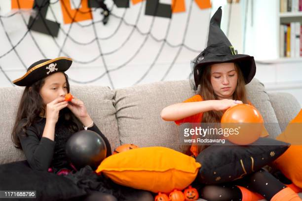 kid girl blowing a balloon in halloween celebrate party - fille moche photos et images de collection