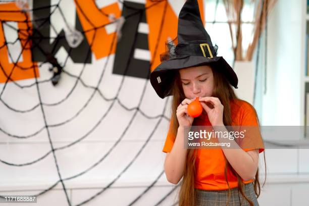 kid girl blowing a balloon in halloween celebrate party - ugly witches stock photos and pictures
