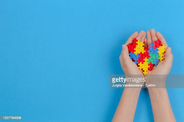 kid hand holding colorful heart on blue background. world autism awareness day concept. - autismo fotografías e imágenes de stock