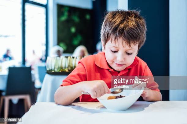 Kid having chocolate ice cream with a spoon indoors (home interior)