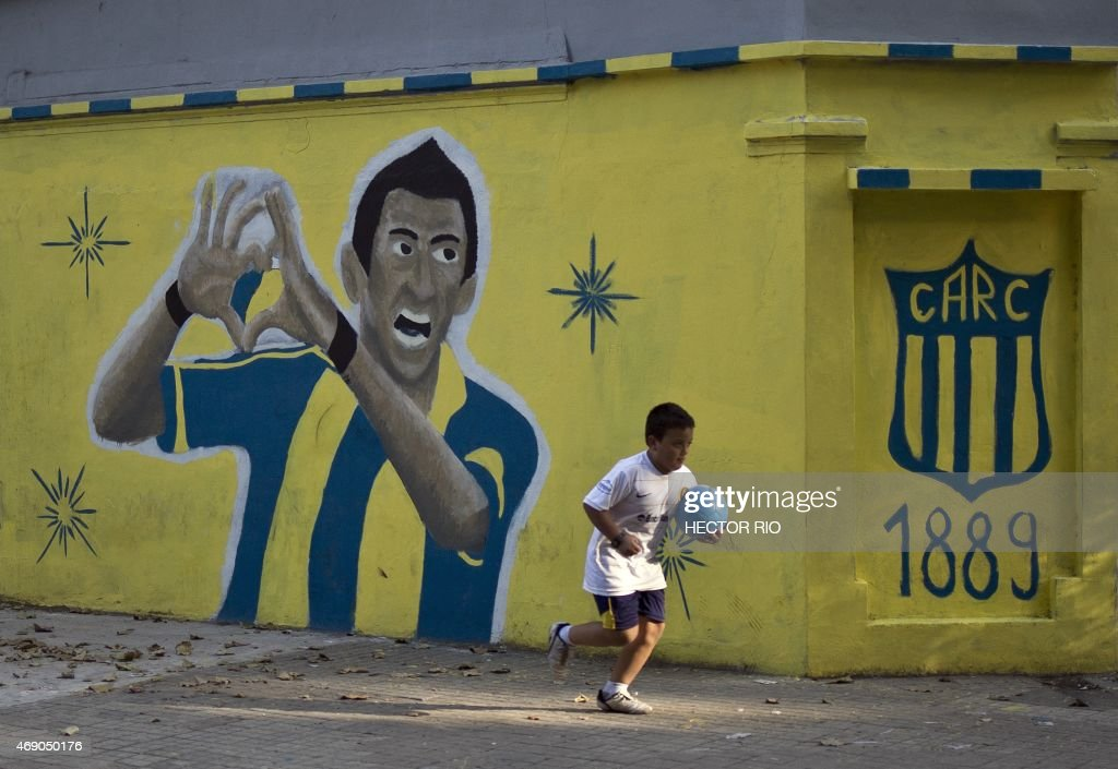 A kid holding a ball runs past a mural depicting Argentine footballer Angel Di Maria painted in a corner near the Gigante de Arroyito stadium of Rosario Central football club in Rosario, Santa Fe province, some 350 km northwest of Buenos Aires on April 5, 2015.
