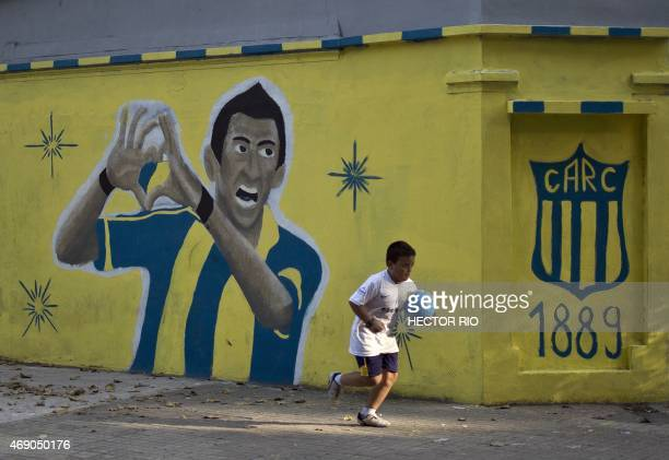 A kid holding a ball runs past a mural depicting Argentine footballer Angel Di Maria painted in a corner near the Gigante de Arroyito stadium of...