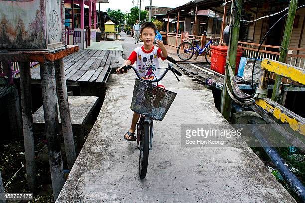 """Kid holding a toy gun while riding on a bicycle at Pulau Ketam which literally translated as """"Crab Island"""". It is small island located off the coast..."""