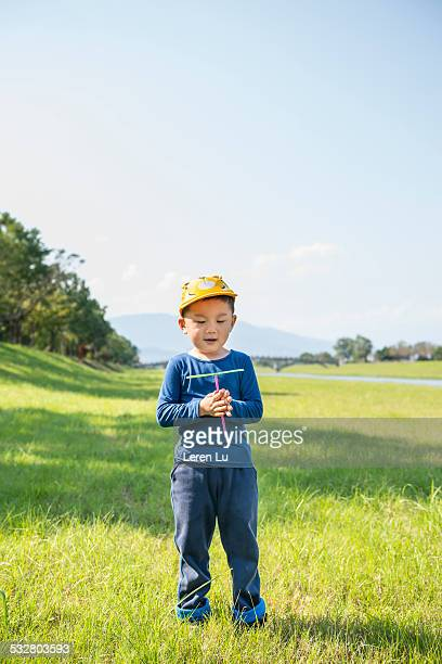 kid holding bamboo dragonfly on grass - leren stock pictures, royalty-free photos & images