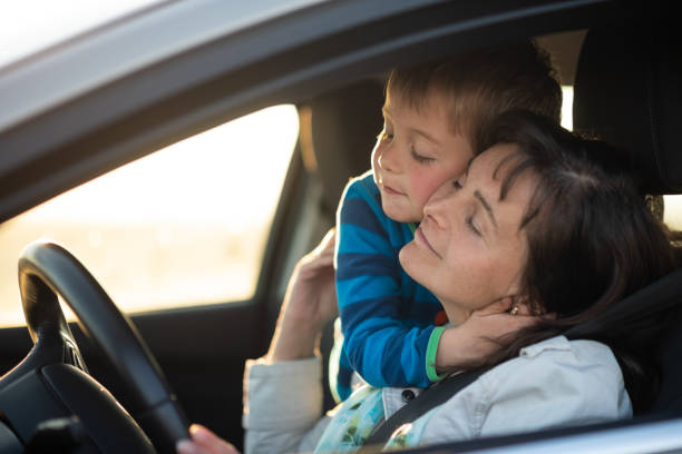 Kid hugging mother driving car