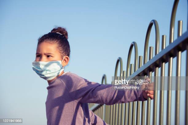 a kid in face mask dreaming of the freedom of movement, staying at backyard, gripping fence rods. - child behind bars stock pictures, royalty-free photos & images