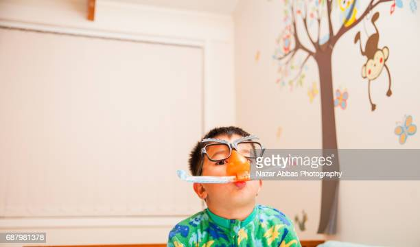 Kid In His Bedroom On His Bed Having Fun With Comedian Glasses.